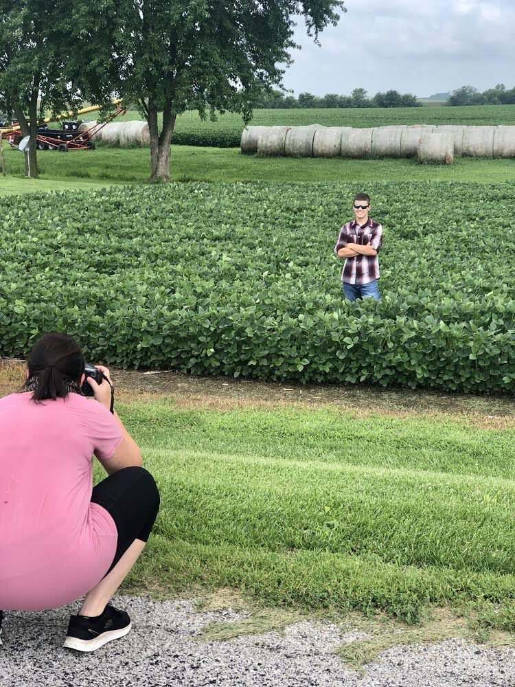 senior pictures on the farm in a field of nutech beans